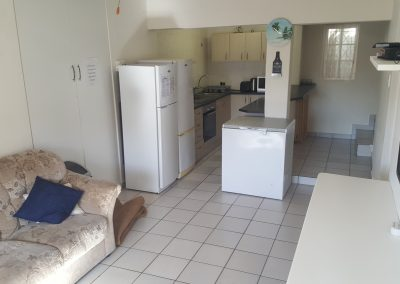 Fully equipped, open plan kitchen with glass top stove.
